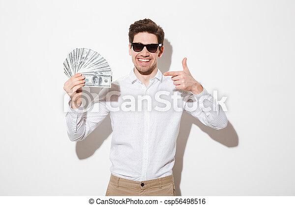 משקפי שמש, חולצה, להצביע, לשמח, קיר, כסף, מעל, דולר, הפרד, הרבה, פדה, אצבע, עשיר, לבן, איש, צל, שמח - csp56498516